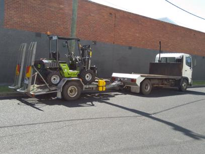 Truck and rough terrain forklift delivering palletised tiles and pavers.